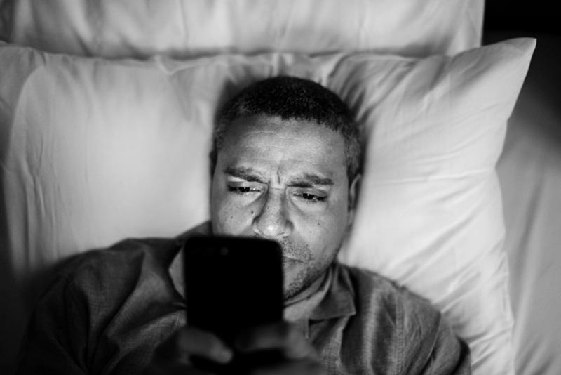 ผู้ชายเล่นโทรศัพท์ก่อนนอน